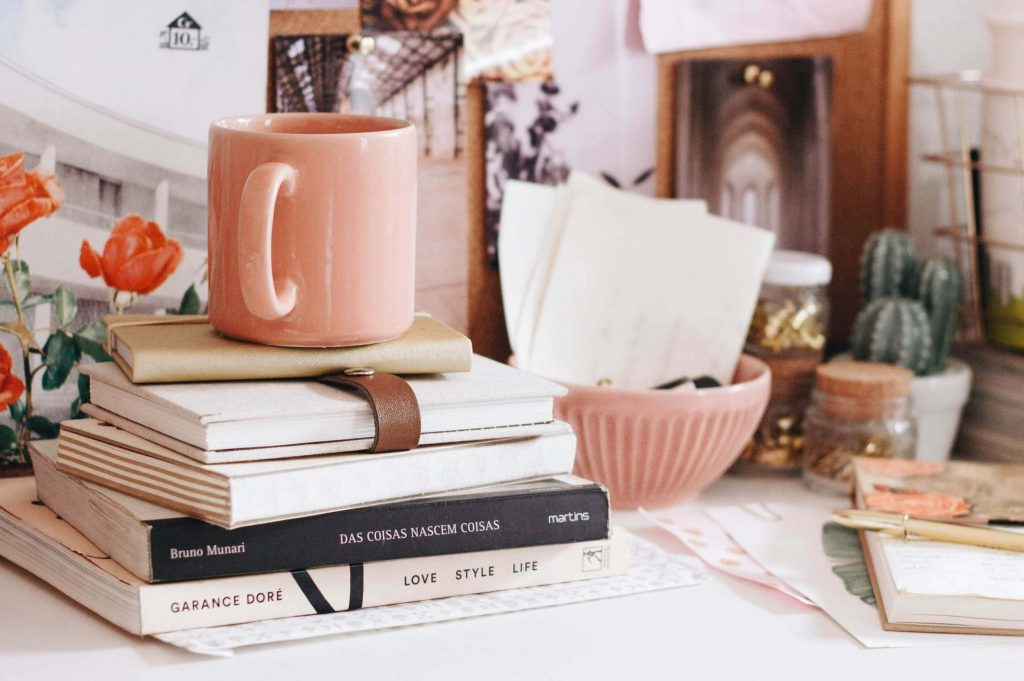 Desk with stack of books and pink mug